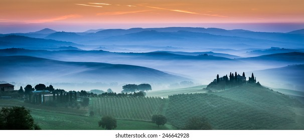 Beautiful green fields and meadows at sunset in Tuscany