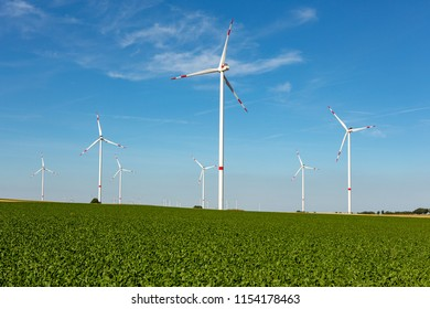 Beautiful green hill with white wind turbines with red stripes generating electricity on a bright blue cloudy sky.