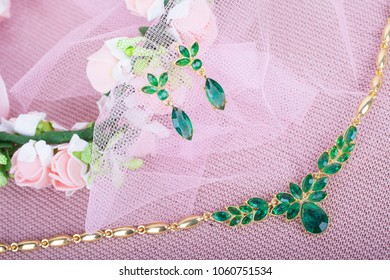 Beautiful green jewelry set on a pink background
