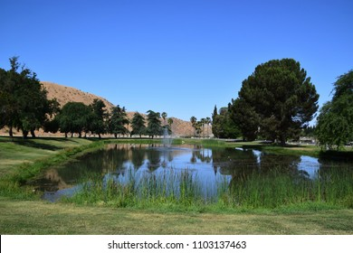 Beautiful green landscape of the lake with trees and golden mountains in the background, it is the beginning of summer season in Kern County at Hart Memorial Park, Bakersfield, CA.