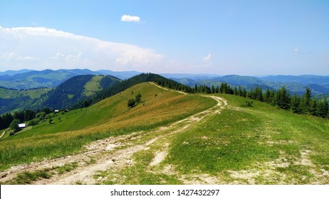 Beautiful green landscape of meadows and trees, blue sky with clouds from the mountain at Bukovinsky Pass