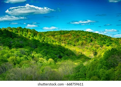 Beautiful green mountains and valleys in the springtime with partly cloudy blue skies