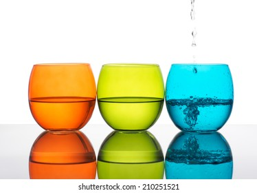 Beautiful green orange and turquoise glasses of water, one being poured. Hydration, healthy living..
