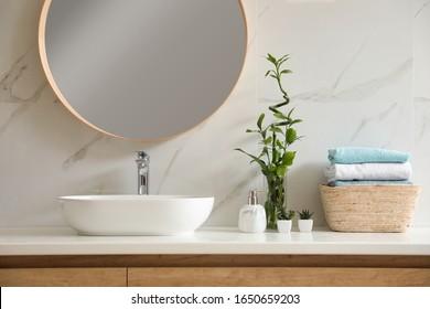 Beautiful green plants near vessel sink on countertop in bathroom. Interior design elements