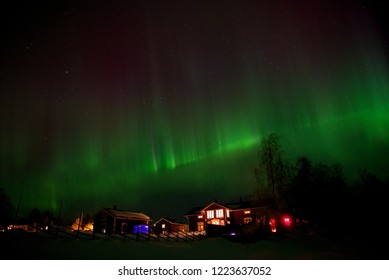 Beautiful Green and Purple Northern Light (Auroraborealis) above some houses in Sweden
