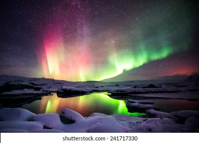 A beautiful green and red aurora dancing over the Jokulsarlon lagoon, Iceland