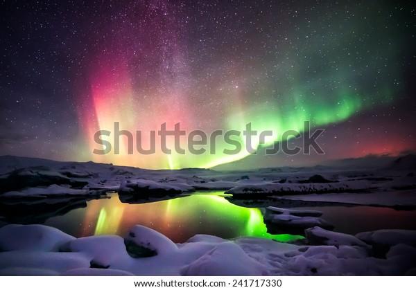 Красивая зеленая и красная аврора, танцующая над лагуной Йокулсарлон, Исландия