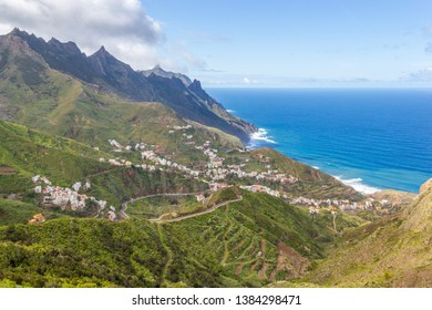 Beautiful green slopes of mountains in Anaga biosphere reserve with roads leading to small village Taganana and blue Atlantic ocean on the background