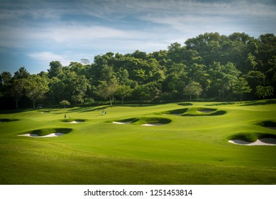 The beautiful green view of green grass and sand banker on golf course with cloudy sky background.