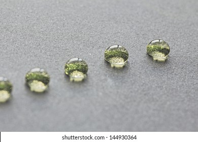 beautiful green water drops in a row, on grey background