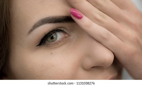 Beautiful green-eyed woman close a half of her face with hand