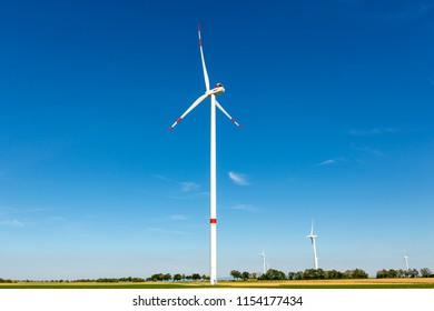 Beautiful green/yellow landscape with white wind turbines with red stripes generating electricity on a bright blue cloudy sky.