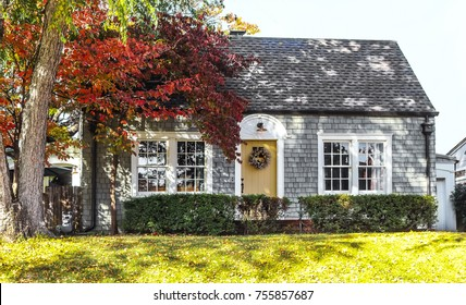Beautiful grey wood shingle cottage with autumn trees and wreath on door