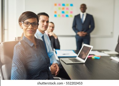 Beautiful grinning professional woman wearing eyeglasses seated with male co-workers and team leader in conference room at work