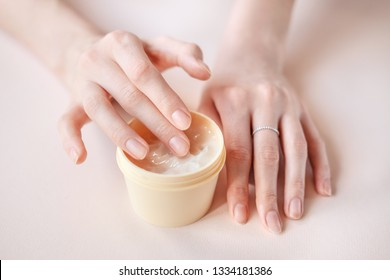 Beautiful groomed woman's hands with body and skin cream on a light background. Nourishing oil for clean and soft skin in winter time. Healthcare concept.