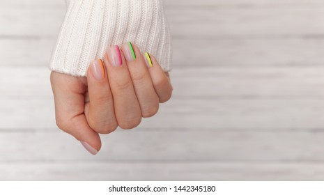 Beautiful groomed woman's hands with colored nails on the wooden background. Manicure, pedicure beauty salon concept. Empty place for text or logo.