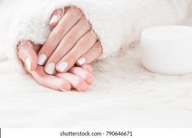 Beautiful groomed woman's hands with cream jar on the fluffy blanket. Moisturizing cream for clean and soft skin in winter time. Manicure beauty salon. Healthcare concept.
