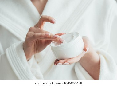 Beautiful groomed woman's hands holding a cream jar on the fluffy blanket. Moisturizing cream for clean and soft skin in winter time. Manicure beauty salon. Healthcare concept. Spa. Studio shot.