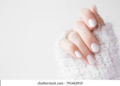 Beautiful groomed woman's hands with white nails on the light gray background. Nail varnishing in white color. Manicure, pedicure beauty salon concept. Empty place for text or logo.