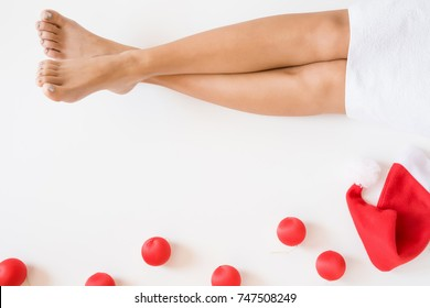 Beautiful, groomed woman's legs with red Santa Claus hat. Cares about clean and soft skin. Beauty spa salon concept. Relax at Christmas time. Empty place for a text.