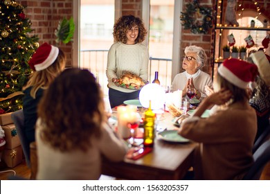 Beautiful group of women smiling happy and confident. Showing roasted turkey celebrating christmas at home