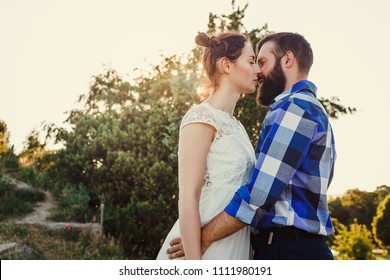 Beautiful guy and girl hugging and kissing. Love story photo on outdoor in sunset light. Couple in love. Pretty girl and brutal bearded guy in outdoor.