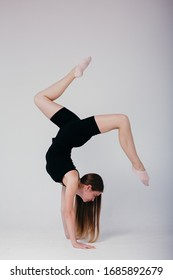 Beautiful gymnast in black sportswear standing on his hands on white background. Sporty girl doing a handstand