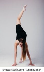 Beautiful gymnast in black sportswear standing on his hands on white background. Sporty girl doing a handstand.