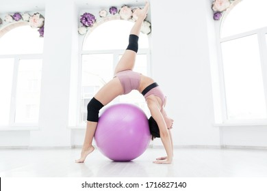 Beautiful gymnast in pink sportswear working on her flexibility with bridge exercise and raised leg with a pilates ball