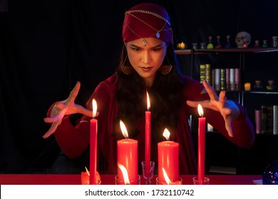 Beautiful Gypsy fortune teller woman casting a magical spell over candle while predicting the future. Divine magic, Forecast esoteric astrology superstition, magical power, alchemy, Black magic.