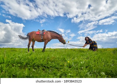 Beautiful gypsy girl leads a stubborn, unruly horse in field with green glass in summer day and blue sky and white clouds background. Woman in ethnic dress tries to steal a horse. Model and big animal
