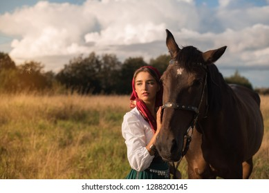 beautiful gypsy with a horse in the field in summer