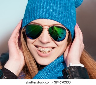 Beautiful haired hair woman, has happy fun cheerful smiling face, cute lips, white teeth and ceramic braces. Dressed in blue knitted hat and scarf. Portrait nature. Sunny day. Instagram style filter.