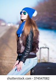 Beautiful haired sexy woman, dressed blue jeans, hat and scarf, fur jacket, sunglasses. Has long hair and elegant slim body, walking to road and holding suitcase. Portrait urban city. Real lady.