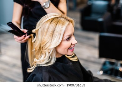 Beautiful hairstyle of blond middle-aged woman in modern hair salon.
