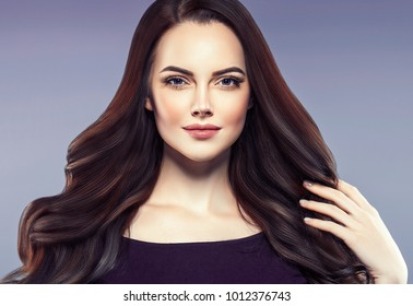 Beautiful hairstyle female with long brunette hair woman over light background