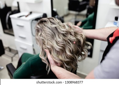Beautiful hairstyle of mature woman after dying hair and making highlights in hair salon.