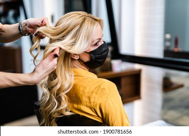 Beautiful hairstyle of middle-aged woman with protective face mask after dyeing hair in hair salon.