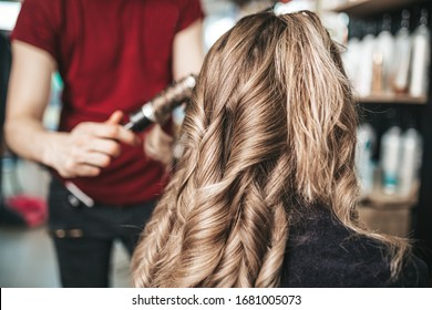 Beautiful hairstyle of woman after dyeing hair and making highlights in hair salon.