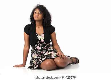 Beautiful Haitian African American teenage girl wearing a floral dress and sitting on the floor against a white background.