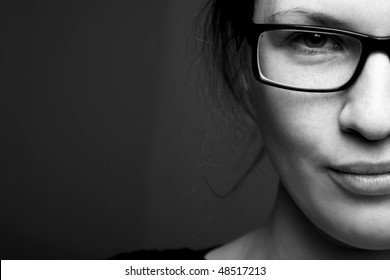Beautiful half face woman in glasess llooks into the camera