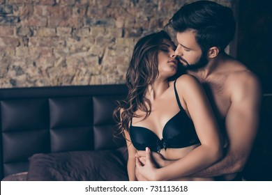Beautiful half naked brunet young couple is embracing in the bed room, about to have sex, so tender, romantic, tempting, sensual. True love and feelings, gentle touch and caress