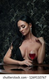 Beautiful half naked woman with glass of wine covering her breast