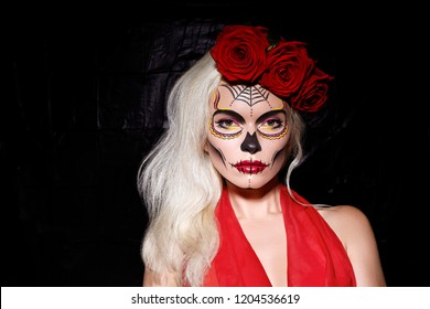 Beautiful Halloween Make-Up Style. Blond Model Wear Sugar Skull Makeup with Red Roses, pale Skin Tones and Waves Hair. Santa Muerte concept