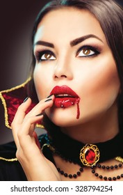 Beautiful Halloween Vampire Woman portrait. Beauty Sexy Vampire lady with blood on her mouth. Fashion Art design. Attractive model girl in Halloween costume and make up