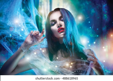 Beautiful Halloween Vampire Woman portrait. Beauty Vampire Witch lady with blood on mouth posing in deep forest, wearing spider web. Fashion Art design. Sexy model girl with Halloween make up