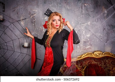Beautiful Halloween Vampire Woman portrait. Beauty Sexy Vampire Witch lady with blood on mouth posing, wearing spider web. Fashion Art design. Mysterious Model girl with Halloween make up