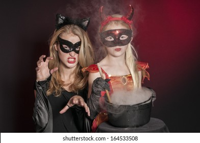 beautiful Halloween vampires with cauldron isolated on dark red background