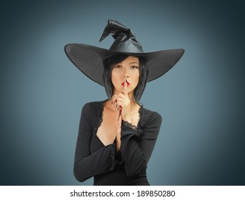 Beautiful Halloween witch makes silence gesture on a gray background