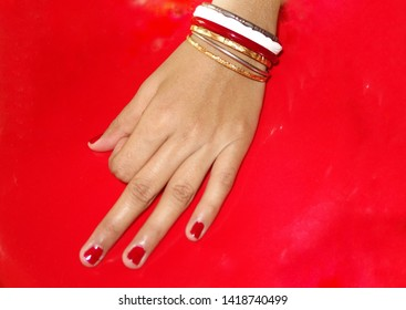 a beautiful hand, finger with cherry or red colour nail polish, bangles, a  traditional white conch bangles, a steel bangle, close up with red background and copy space
